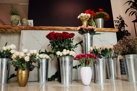counter of the flower shop is filled with zinc vases with bouquets of various colors.