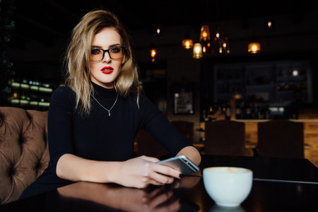 Beautiful fashionable stylish girl sits in a cafe with a cup of coffee. Zdjęcie Seryjne