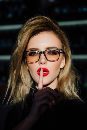 Hush. Woman in glasses ask for silence or secrecy with finger on red lips. shh hand gesture. Zdjęcie Seryjne
