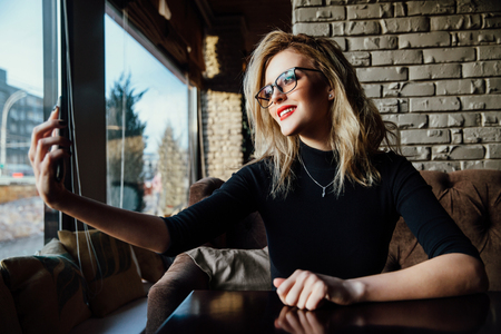 Young beautiful blonde woman taking a selfie in coffee shop. Hipster, red lips, glasses. Zdjęcie Seryjne
