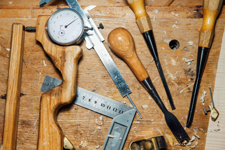Tools on the desktop in the workshop. Making a violin. Wood shavings and dust, creative mess. Stock Photo