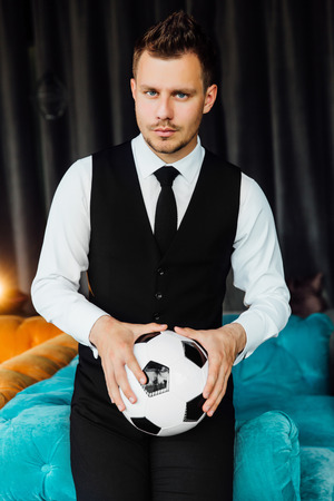 Stylish athletic man in a business costume vest holding a soccer ball. football player.