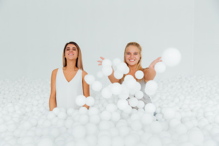 Portrait Happy Girlfriends stand surrounded by white plastic balls in the dry pool.