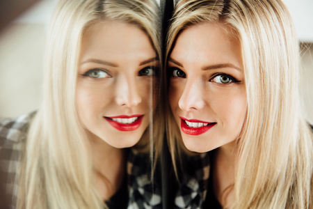 portrait of beautiful young woman blonde girl and her reflection in mirror.