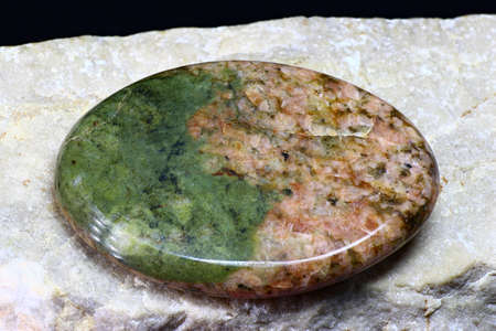 Unakite (granite with green epidote) processed in the form of a cabochon on a white marble background Stock Photo