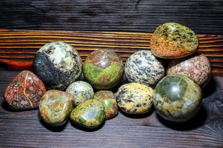 Collection of processed stones of different colors - magmatites - on a wooden background