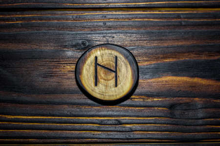 Rune Haglaz (Hagalaz) carved from wood on a wooden background - Elder Futhark