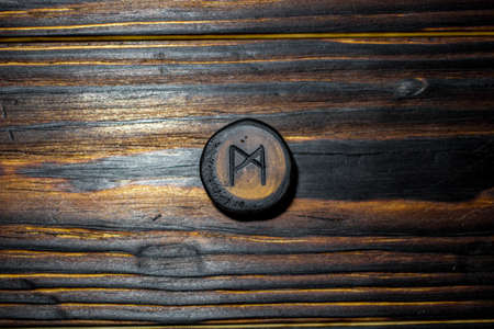Rune Mannaz (Mann) carved from wood on a wooden background - Elder Futhark