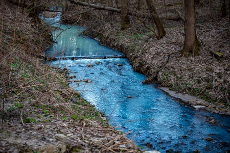 Painted in a bright blue river after illegal discharge of polluting liquid
