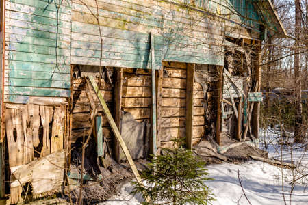 Demolished wooden structure in a forest area in winter. Former pioneer camp in Russia