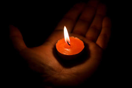 Burning candle on the palm, sorrow and memory