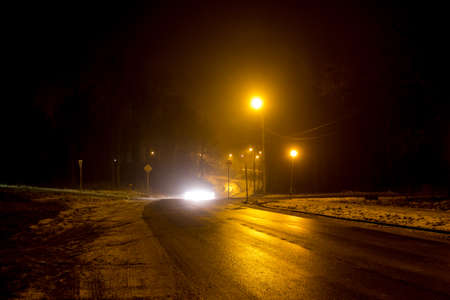 The road at night illuminated by dim lanterns during a thick fog, foggy evening Stock Photo