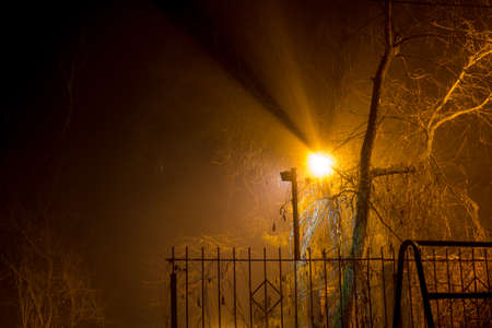 Scattered light from a street lamp at night during a thick fog, foggy evening