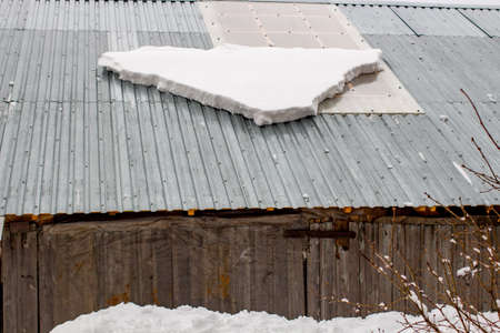 A layer of snow in the spring on the roof, snow mass drop