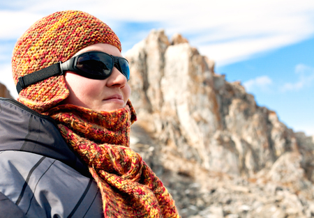 baical: Portrait of a girl in orange scarves and hats against the blue sky and snowy mountains. Sport mountain sunglasses. Bright sunny winter day. Wrapped in a scarf. Olkhon Island on Lake Baikal.. Traveler. Soothe.