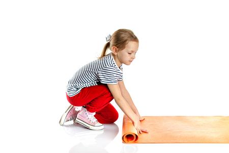 ittle: ittle girl doing gymnastic exercises on a yoga mat. doing fitness exercise on an exercise mat. Isolated on white background