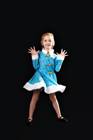 splayed: Little girl jumping in the air. In the blue dress. black ballet flats. Pulls socks. Splayed white hair. Little girl 5-7 years, isolated on a gray background.