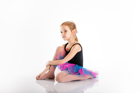 faldas: niña a estudiar danza. Deportes traje de baño. Falda mullida púrpura. Niña 5-7 años, aislado en un fondo blanco. hacer ejercicios y estiramientos en el suelo Foto de archivo
