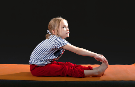 caucasian appearance: Little girl 5-7 years, doing exercises on the mat for yoga. Pull the hands to the feet. The slopes. exercise floor. Orange yoga mat. Red tracksuit. striped shirt. Caucasian appearance. Gray background Stock Photo