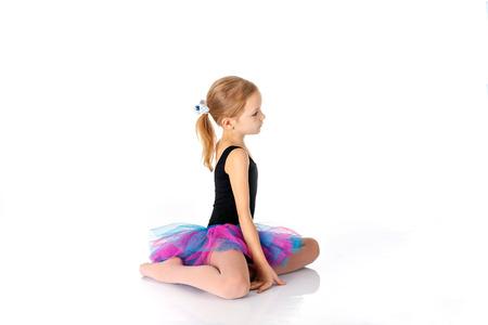 little ballerina sitting on floor on white backgroundn studio posing on camera.  Little girl studying dance is busy performing exercises on the floor. girl 5-7 years in Sports Swimsuit purple and fluffy skirt.