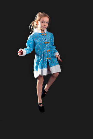 splayed: Little girl jumping in the air. In the blue dress. black ballet flats. Pulls socks. Splayed white hair. Little girl 5-7 years, isolated on a gray background. The European appearance. Stock Photo