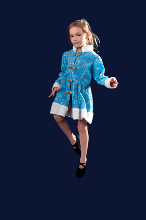 splayed: Little girl jumping in the air. In the blue dress. black ballet flats. Splayed white hair. Little girl 5-7 years, isolated on a gray background. The European appearance.