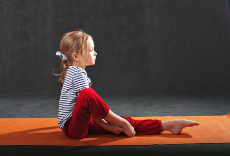 caucasian appearance: Little girl 5-7 years, doing exercises on the mat for yoga. Pull the hands to the feet. The slopes. exercise floor. Orange yoga mat. Gray background. Red tracksuit. striped shirt. Caucasian appearance.