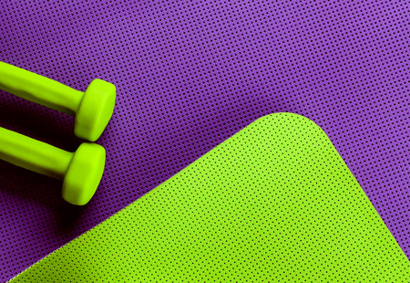 bright colors: purple and green yoga mat. Two green dumbbell for fitness. Bright colors. training Modern