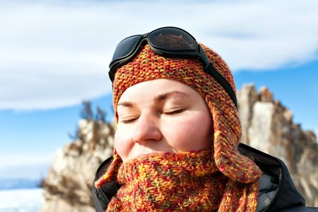 baical: Portrait of a girl in orange scarves and hats against the blue sky and snowy mountains. Closed eyes. Sport mountain sunglasses. Bright sunny winter day. Wrapped in a scarf. Shaman on Lake Baikal. Olkhon Island. Traveler. Soothe.