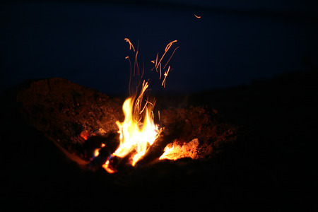 near: Hiking tourist have a rest  at night near campfire. A campfire near a lake Stock Photo