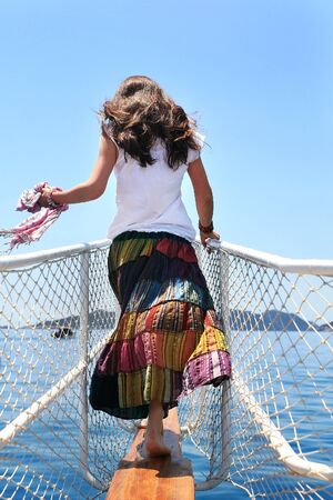 adult cruise: Girl in a long skirt patchwork on the deck, watching the sea in summer sunny day Stock Photo