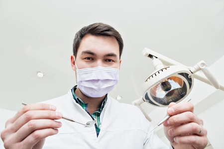 dentist at work: Dentist leaned over the patient.. in the dentists chair in the clinic. The doctor in a mask and with the tool. Admission to the dentists office.v Stock Photo