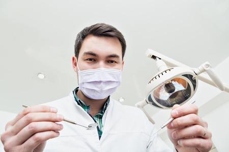 Tandarts leunde over de patiënt .. in de stoel van de tandarts in de kliniek. De arts in een masker en het werktuig. Toelating tot office.v de tandarts