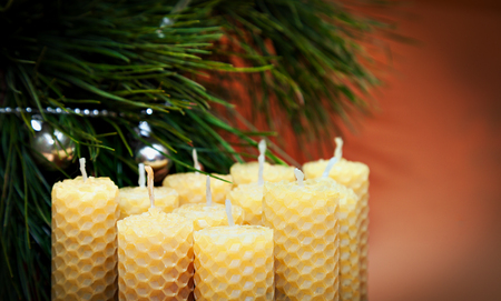 beeswax candle: romantic candles from natural wax twisted with band made for holiday. Candle made of beeswax honeycomb.