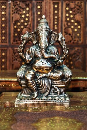 indian artifacts: Buddhism. India. The figure of the Hindu god of wisdom, knowledge and new beginnings Ganesha against wooden background.