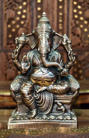 new beginnings: India. Beautiful figure of the Hindu god of wisdom, knowledge and new beginnings Ganesha against wooden background. Buddhism.