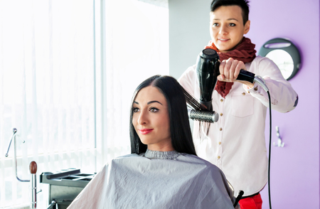caucasian appearance: Beautiful young girl in a beauty salon.  Stylist with hair dryer and a comb in his hand. Model with long black hair in a barber chair. A gray cape. Purple background. Caucasian appearance.