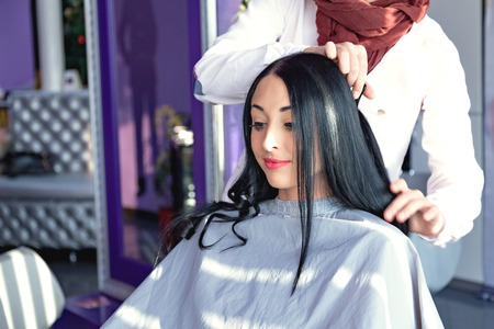 caucasian appearance: Beautiful young girl in a beauty salon. Job hairdresser and stylist. A girl with long black hair in a barber chair. A gray cape. Purple background. Caucasian appearance. doing make-up Stock Photo