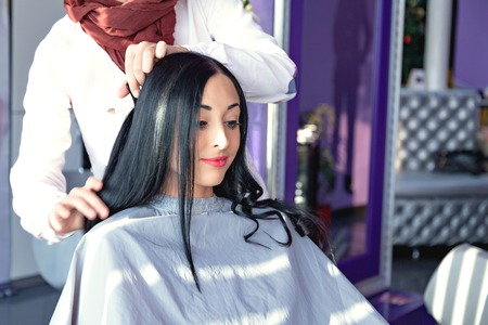 caucasian appearance: young girl in a beauty salon. Job hairdresser and stylist. A girl with long black hair in a barber chair. A gray cape. Purple background. Caucasian appearance. doing make-up Stock Photo
