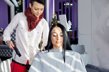 stylists: Beautiful young girl in a beauty salon. Doing make-up. Hairdressers and stylists during operation. Tools hairdresser. A girl with long black hair in a barber chair. Purple background.