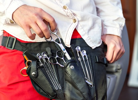 red pants: Cabourg tools. Professional. Clippers and hair brush in the hands of a barber. Red pants and a white shirt.