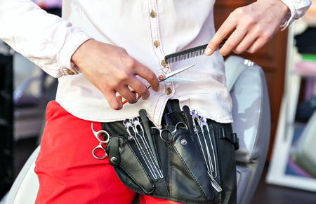 red pants: Cabourg tools. Clippers and hair brush in the hands of a barber. Professional. Red pants and a white shirt.