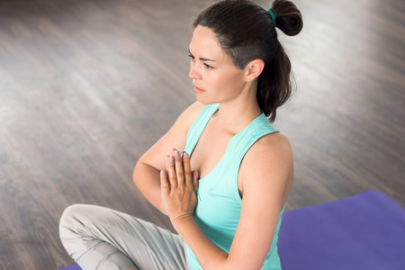 namaste: young beautiful girl is engaged in yoga in a studio. Happy and healthy woman meditating hands in a gesture of Namaste. Yoga at home. Involved in fitness in the morning Stock Photo