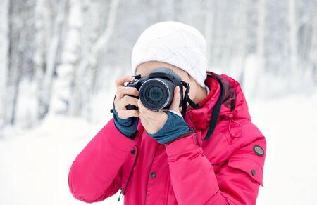 Het meisje met de camera op de achtergrond van de wintersneeuw. Helderroze jas. Fotograaf met de camera. Stockfoto