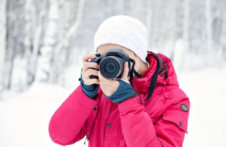 The girl with the camera on the background of winter snow. Bright pink jacket. Photographer with the camera.