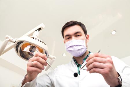 dentista: Dentista que examina los dientes de un paciente en la silla de los dentistas en la clínica dental. El médico en una máscara y con la herramienta. La admisión a la consulta del dentista.