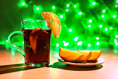 mulled wine spice: Good New Year spirit. red cup of hot mulled wine with orange slices. Green garland. Stock Photo