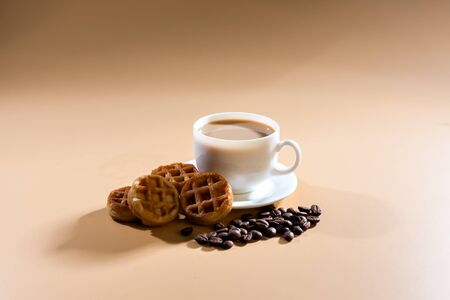 cup four: A white cup of cappuccino on a beige background. Nearby are whole grains of coffee and four soft waffles.