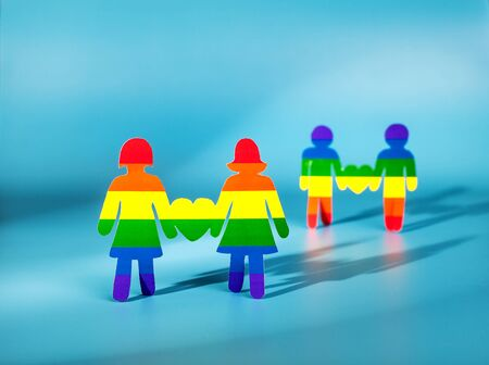 sexo: Dos humana papel. corazón del arco iris. colores de la bandera de la homosexualidad. la relación entre las dos chicas. amor del mismo sexo. Gay y lesbi. Minorías. Cuestiones de género. emblema gay.