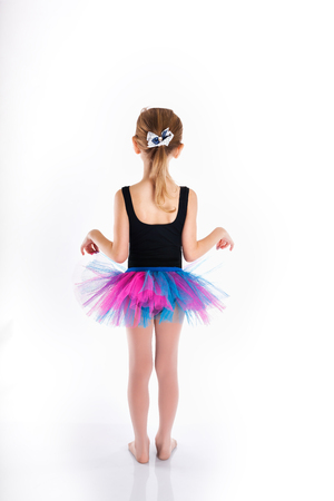 maillot de bain fille: Drôle petite fille à étudier la danse. maillot de bain Sport. jupe pourpre. Petite fille isolée sur fond blanc. Adorable petite fille sautant en l'air.